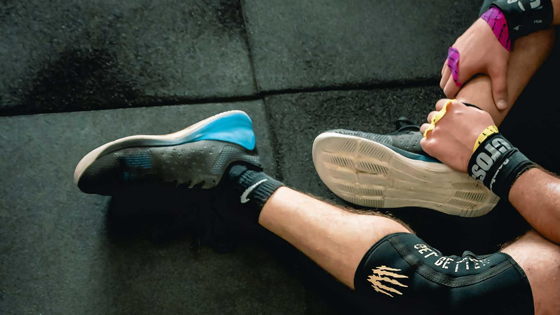 Lähikuvassa toiminnallisen harjoittelun treenaaja lattialla istumassa.